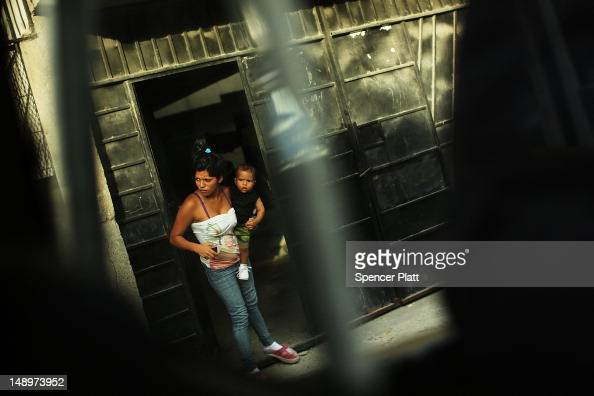A woman and her son look out of a doorway in a neighborhood with heavy gang violence on July 20 2012 in Tegucigalpa Honduras Honduras now has the...