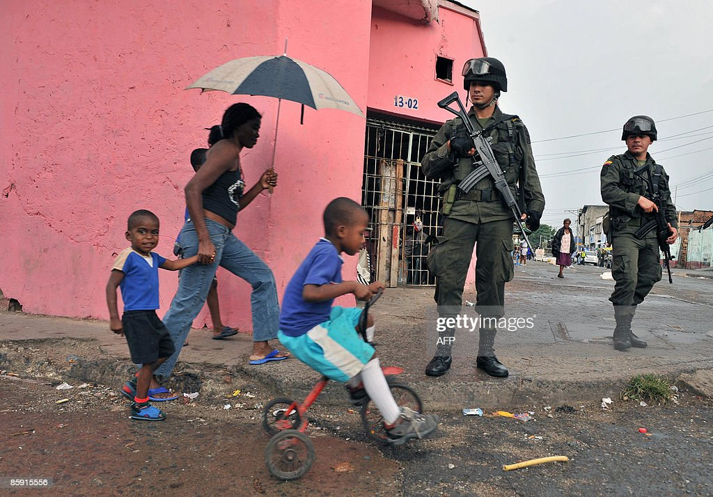 A woman and her sons walk past policemen during an operation against crime on April 11 in Cali department of Valle del Cauca Colombia AFP PHOTO/Luis...
