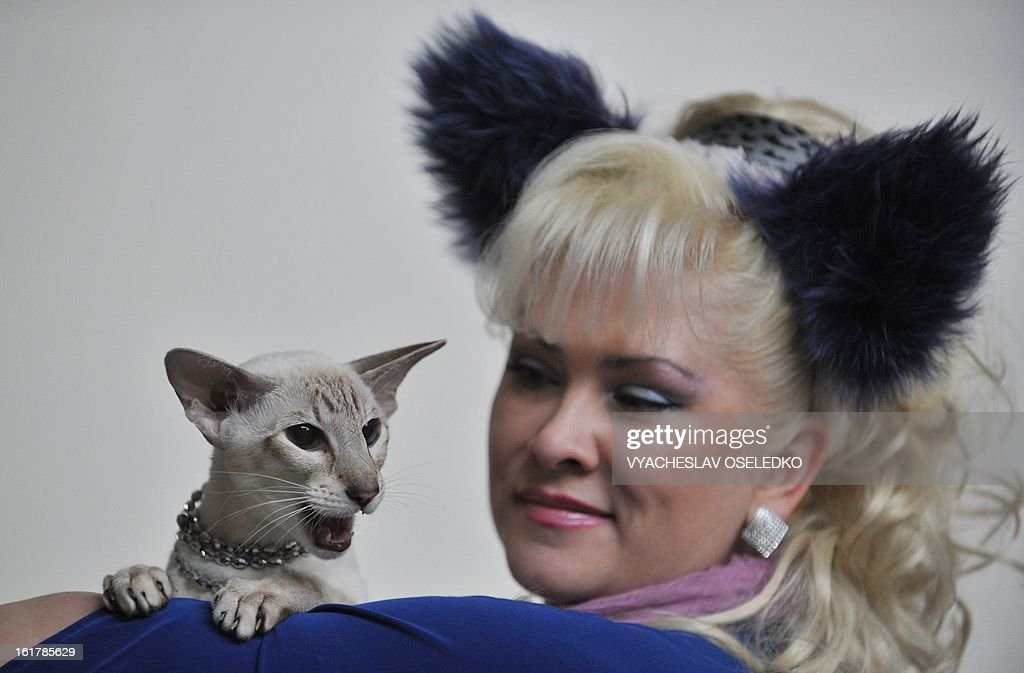 A woman and her Sphynx cat pose during a cat exhibition in the Kyrgyzstan's capital Bishkek on February 16, 2013. Cats owners from Kyrgyzstan, Kazakhstan and Uzbekistan gathered today in Bishkek to show off their pets.