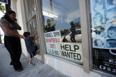 A woman and her stand wait outside a beauty salon with a 'Help Wanted' sign in the window in East Los Angeles California on September 3 2010 A...