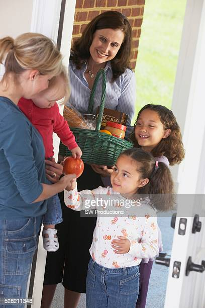 A Woman And Her Two Daughters Delivering A Basket Of Food To A Woman With Her Child