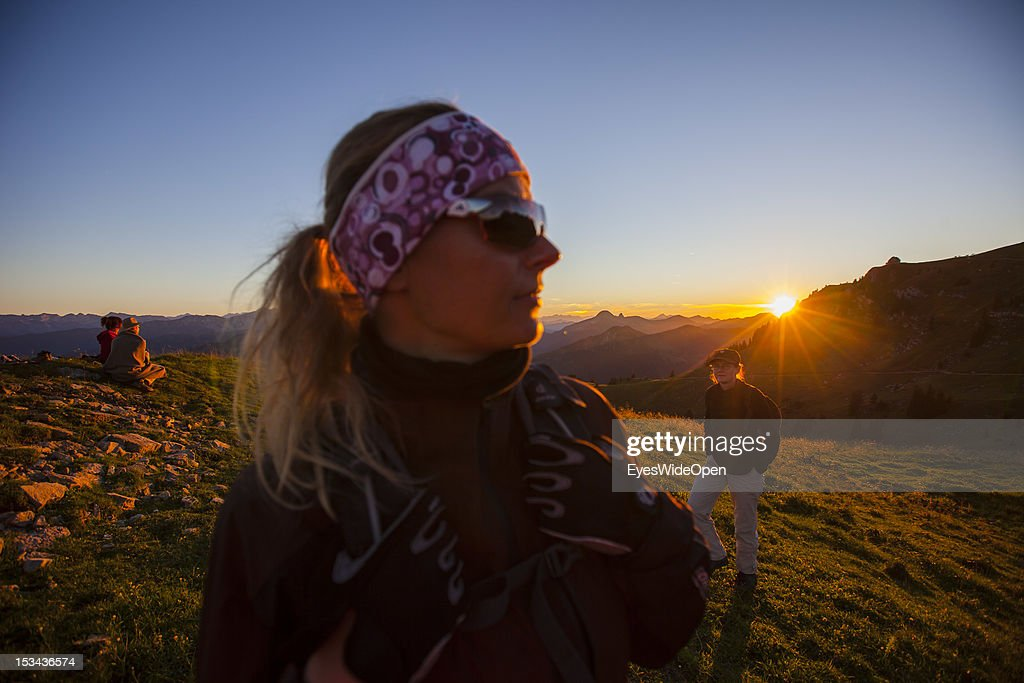 A woman and hikers are watching the sunset at the mountain of Rotwand with a panoramic view of the so called Blue Bavarian Alps on August 29, 2012 in Spitzingsee, Bavaria, Germany.
