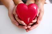 Woman and kid hold red toy heart in arms closeup. Female give birth to life, palm hug, diagnosis aid, healthy pregnancy, feel peace, donation service, souls together, abortion concept