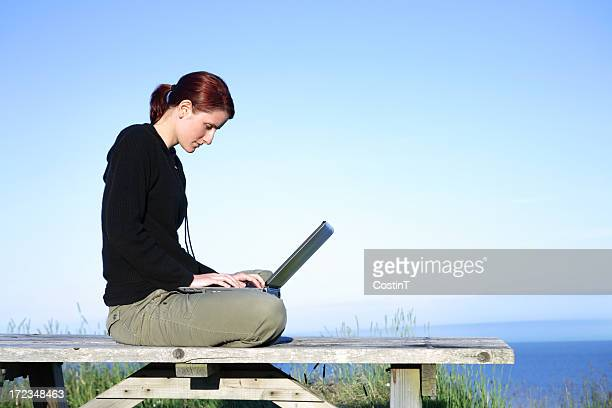 Woman and laptop on the shore