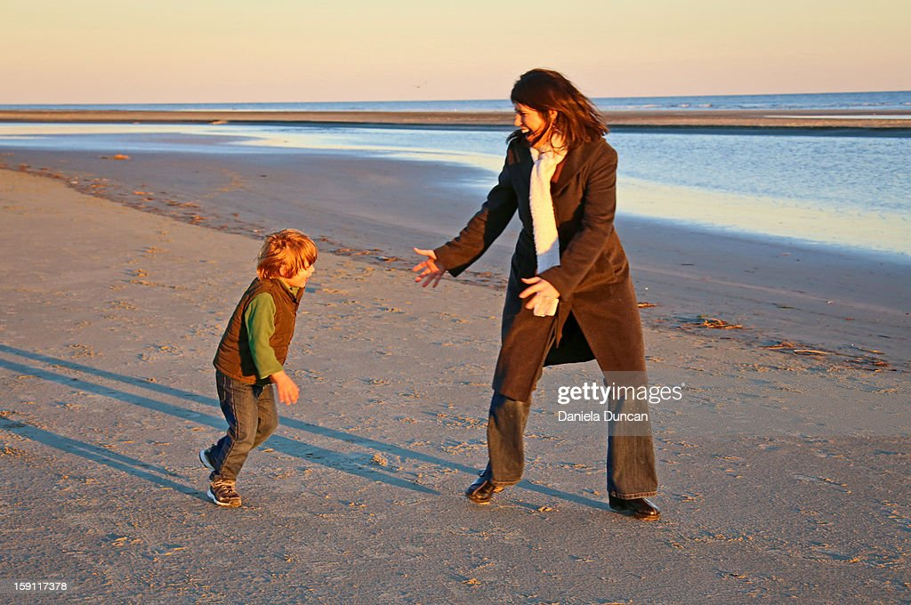Woman and little boy playing at the beach : Stock Photo