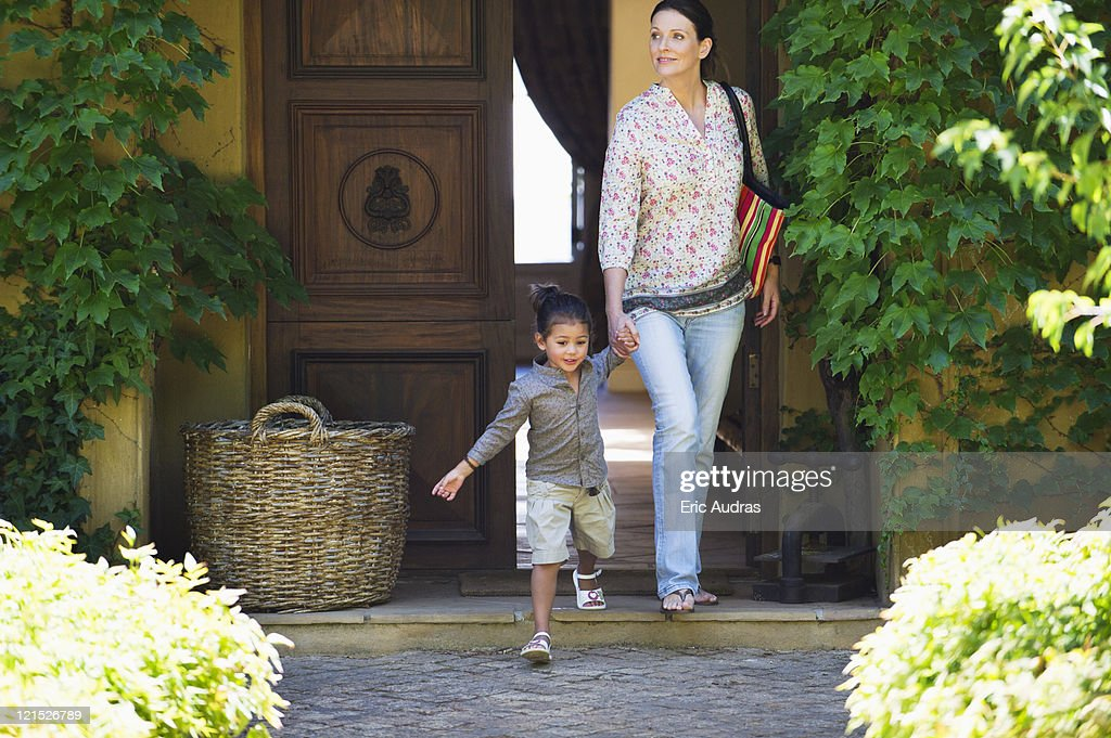 Woman and little girl walking out of their house holding hands