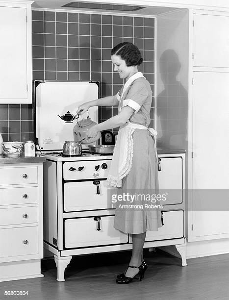 Woman and maid standing over stove pouring water into saucepan