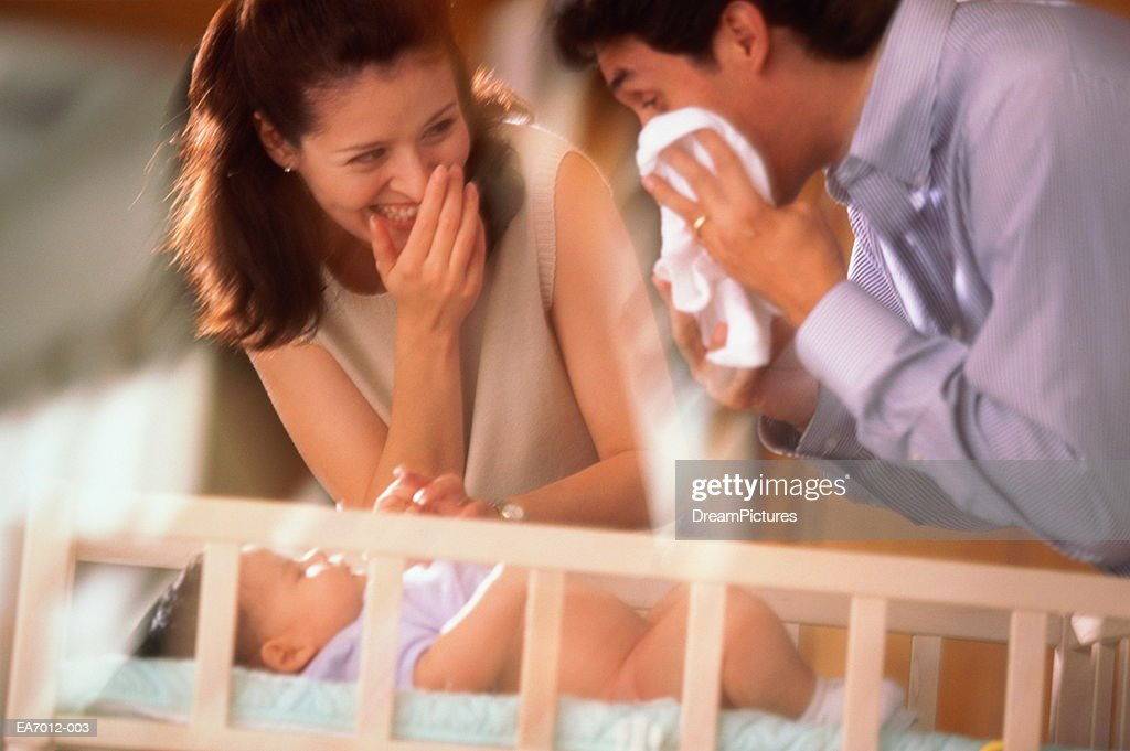 Woman and man changing baby's (3-6 months) nappy : Stock Photo