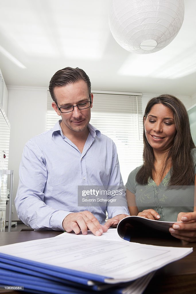 Woman and man doing paperwork at home : Stock Photo