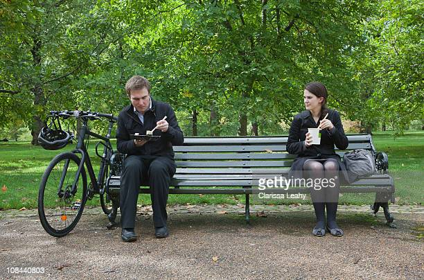 Woman and man eating lunch on park bench