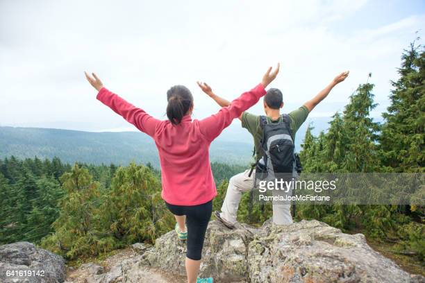 Woman and Man Embracing Nature with Open Arms from Mountaintop