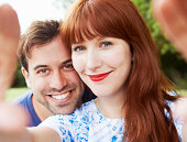 woman and man holding up mobile to take selfie