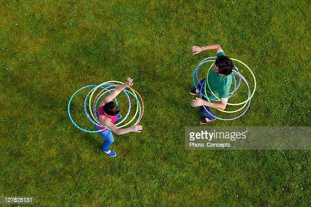 Woman and man hula hooping in grass