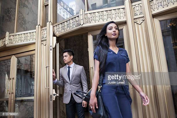 A woman and man in business dress leaving building