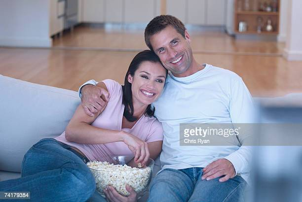 Woman and man on sofa with popcorn watching television