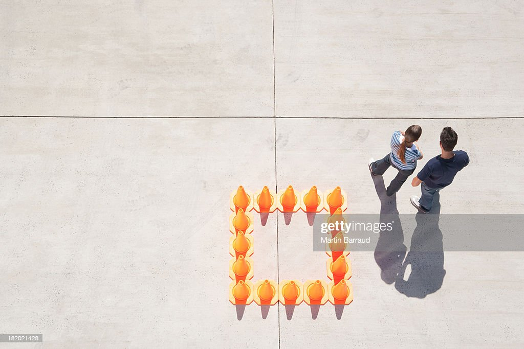 Woman and man outside box of traffic cones : Stock Photo