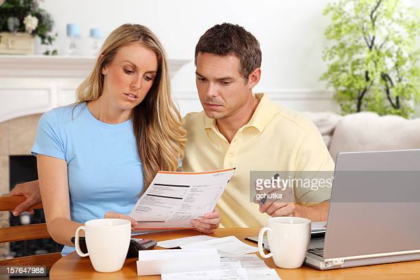 A woman and man paying their paper bills on their laptop
