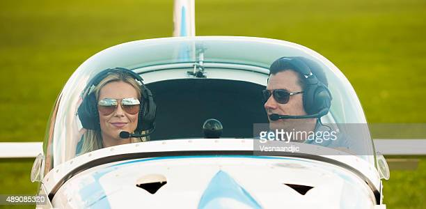 Woman and man pilot looking at camera, preparing for flying