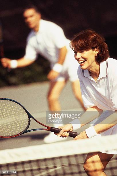 Woman and man playing mixed doubles tennis