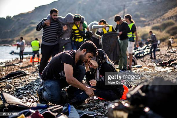 A woman and man react as they arrive with other refugees and migrants on the shores of the Greek island of Lesbos after crossing the Aegean sea from...