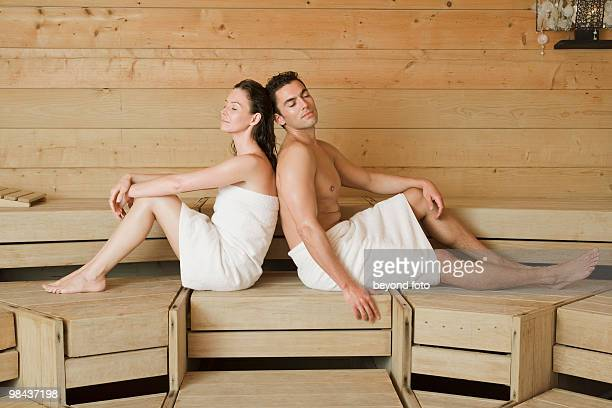 woman and man relaxing in sauna sitting back to back