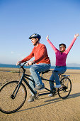 Woman and man riding tandem bicycle