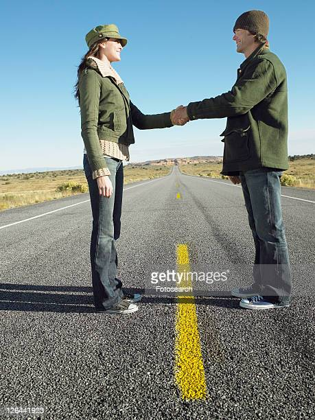 Woman and man shaking hands on highway, low angle view