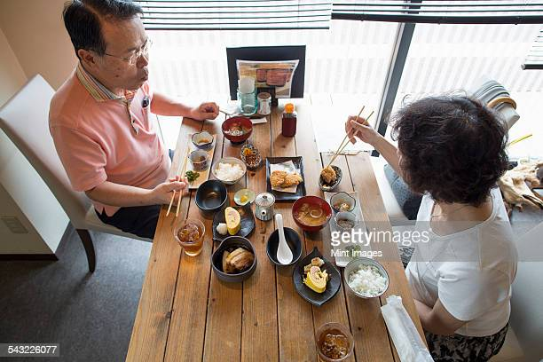 Woman and man sitting at a table, eating Japanese Food with chopsticks.