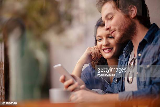 Woman and Man sitting in coffee shop with Phone