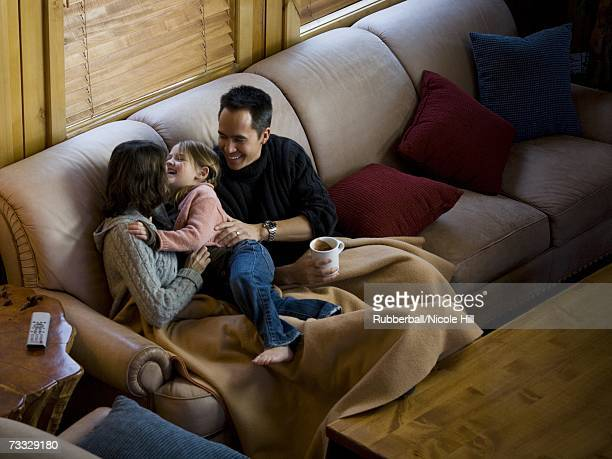 Woman and man snuggling with young girl on sofa