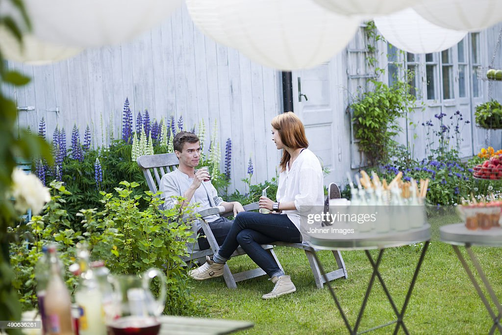 Woman and man talking at garden party