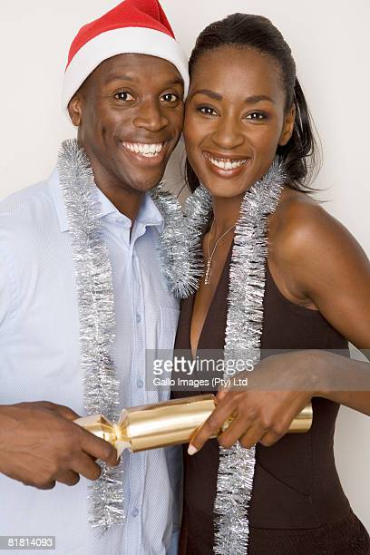 Woman and man with a Christmas hat embracing and pulling a cracker.