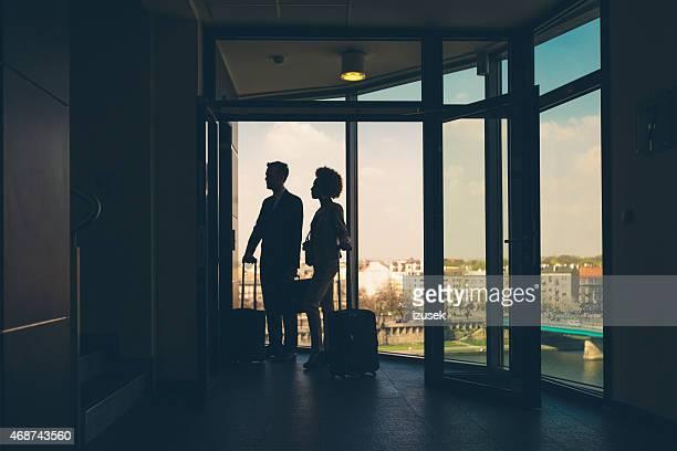 Femme et homme avec des valises en attente pour l'ascenseur de l'hôtel