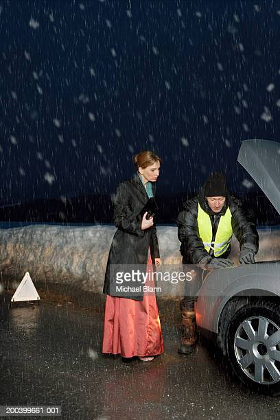 Woman and mechanic looking under car bonnet in snow, night
