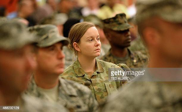 A woman and member of the Australian military forces attend the opening ceremony of the PhilippineUS annual joint military exercises at the military...