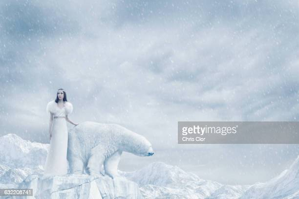 Woman and polar bear standing on glacier