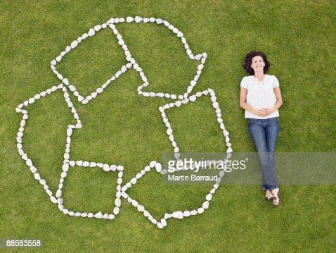 Woman and recycling symbol in grass
