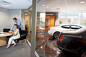 Woman and salesman sitting in car showroom office
