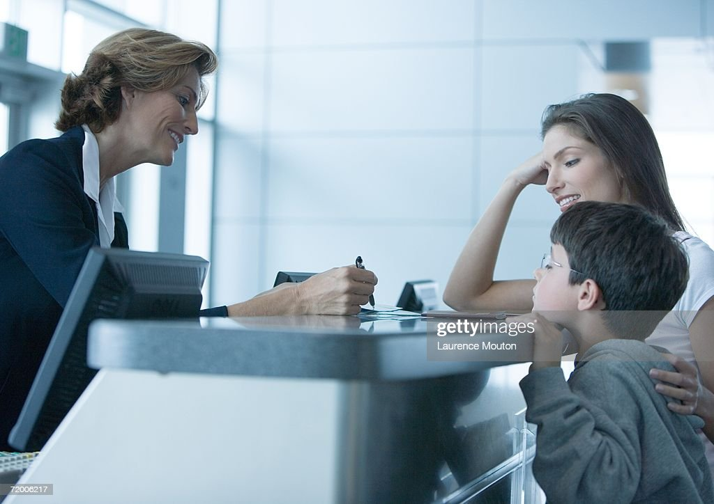 Woman and son standing at check-in counter in airport