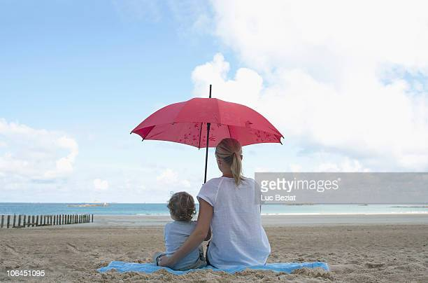 Woman and son under a parasol