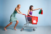 Woman and teen girl in shopping cart action