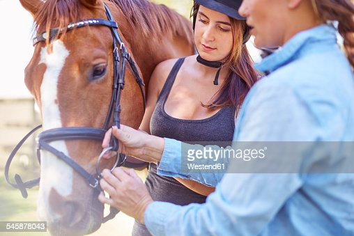 Woman and teenage girl with riding horse