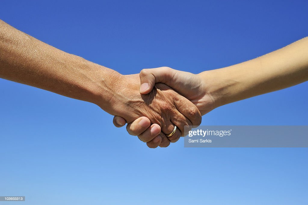 Woman and teenager handshake, on blue sky : Stock Photo