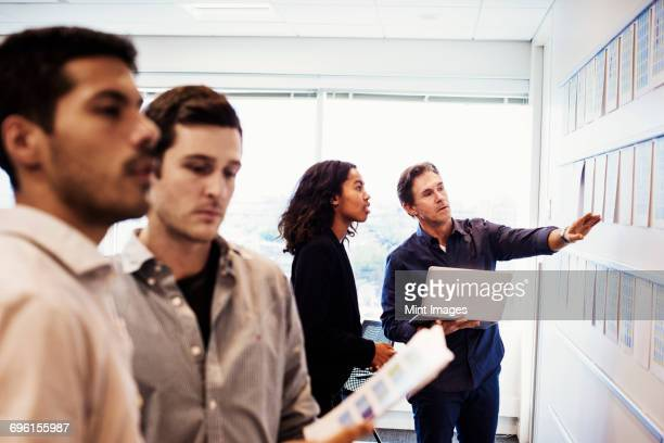 A woman and three men standing in an office looking at a display on a wall.
