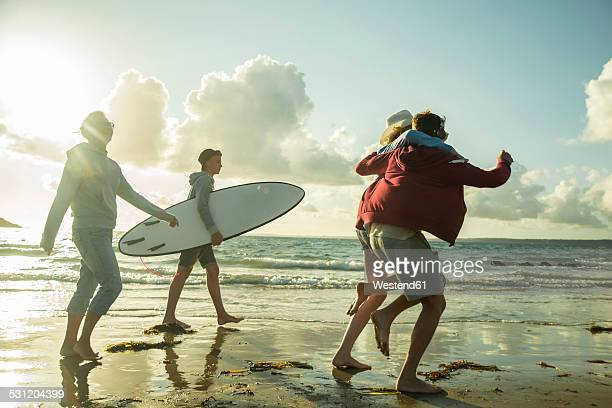 Woman and three teenagers walking at waterside of the sea