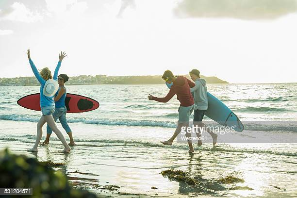 Woman and three teenagers with surfboards running at waterside of the sea