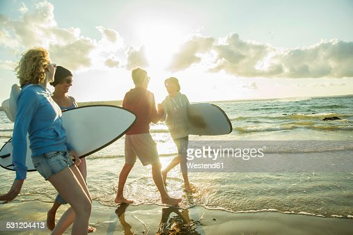 Woman and three teenagers with surfboards walking at waterside of the sea