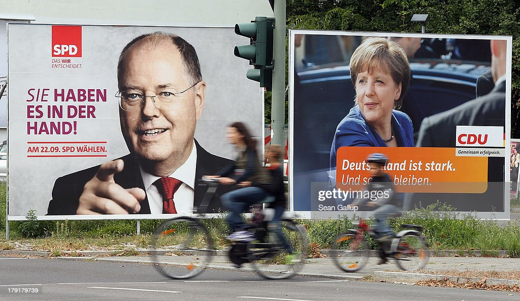 A woman and two children ride bicycles past election campaign billboards featuring German Social Democrats (SPD) chancellor candidate Peer Steinbrueck (L) and German Chancellor and Christian Democrat (CDU) Angela Merkel on September 1, 2013 in Berlin, Germany. The two rivals are scheduled to face off in their first election television debate later today ahead of German elections cheduled for September 22.