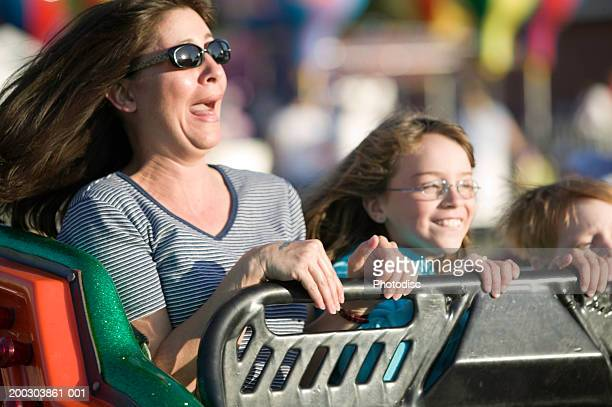 Woman and two children (4-5), (6-7) riding in rollercoaster in amusement park
