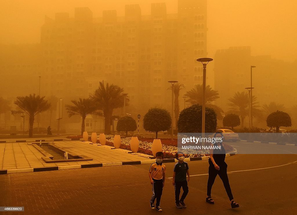 A woman and two children wear medical masks as they cross a street amid a sandstorm that engulfed the city of Dubai on April 02 2015 AFP PHOTO /...
